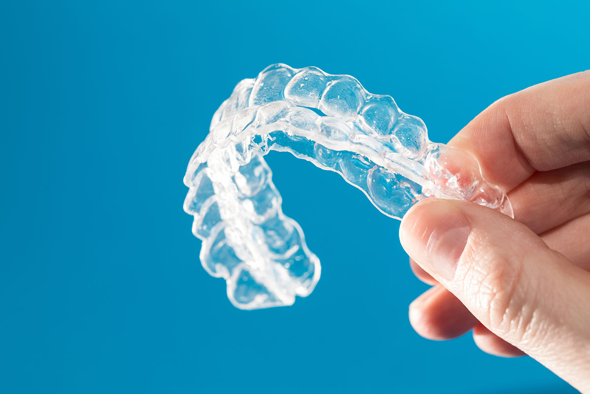 Crystal clear upper and bottom invisible aligner braces held in a mans hand